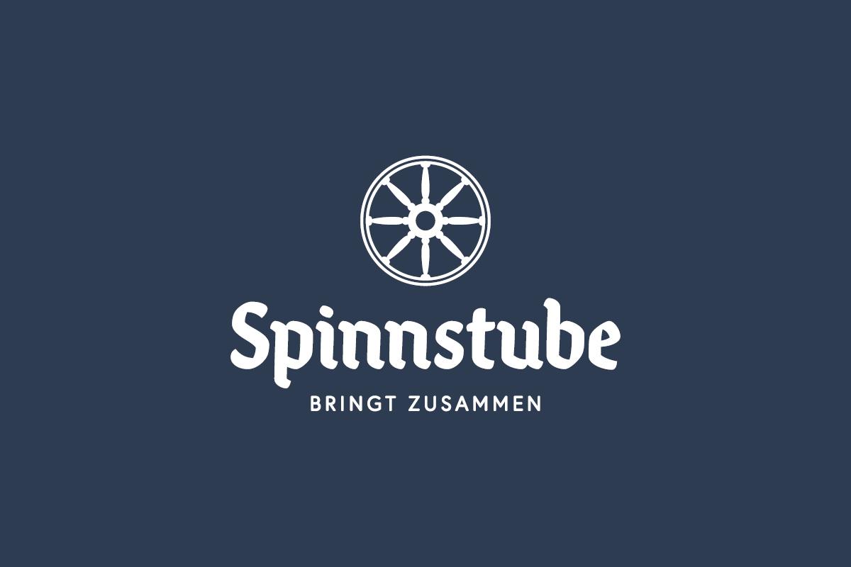 """Weißes Logo auf dunkelblauem Hintergrund, es zeigt ein Spinnrad als Bildmarke mit der Wortmarke """"Spnnstube"""" und der Unterzeile """"bringt zusammen"""""""